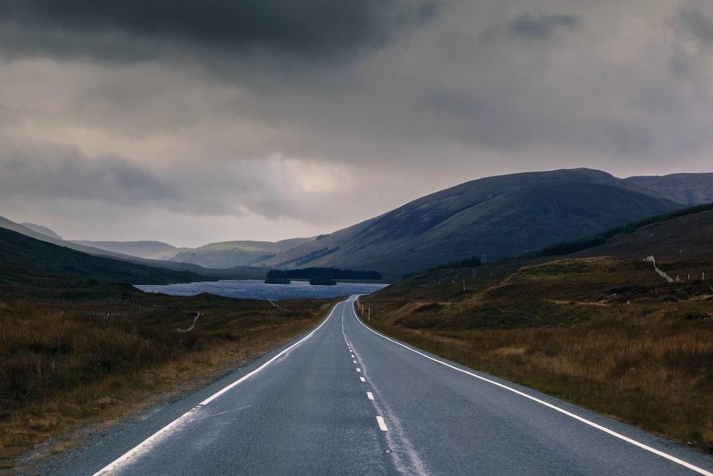 gray asphalt road under nimbus clouds