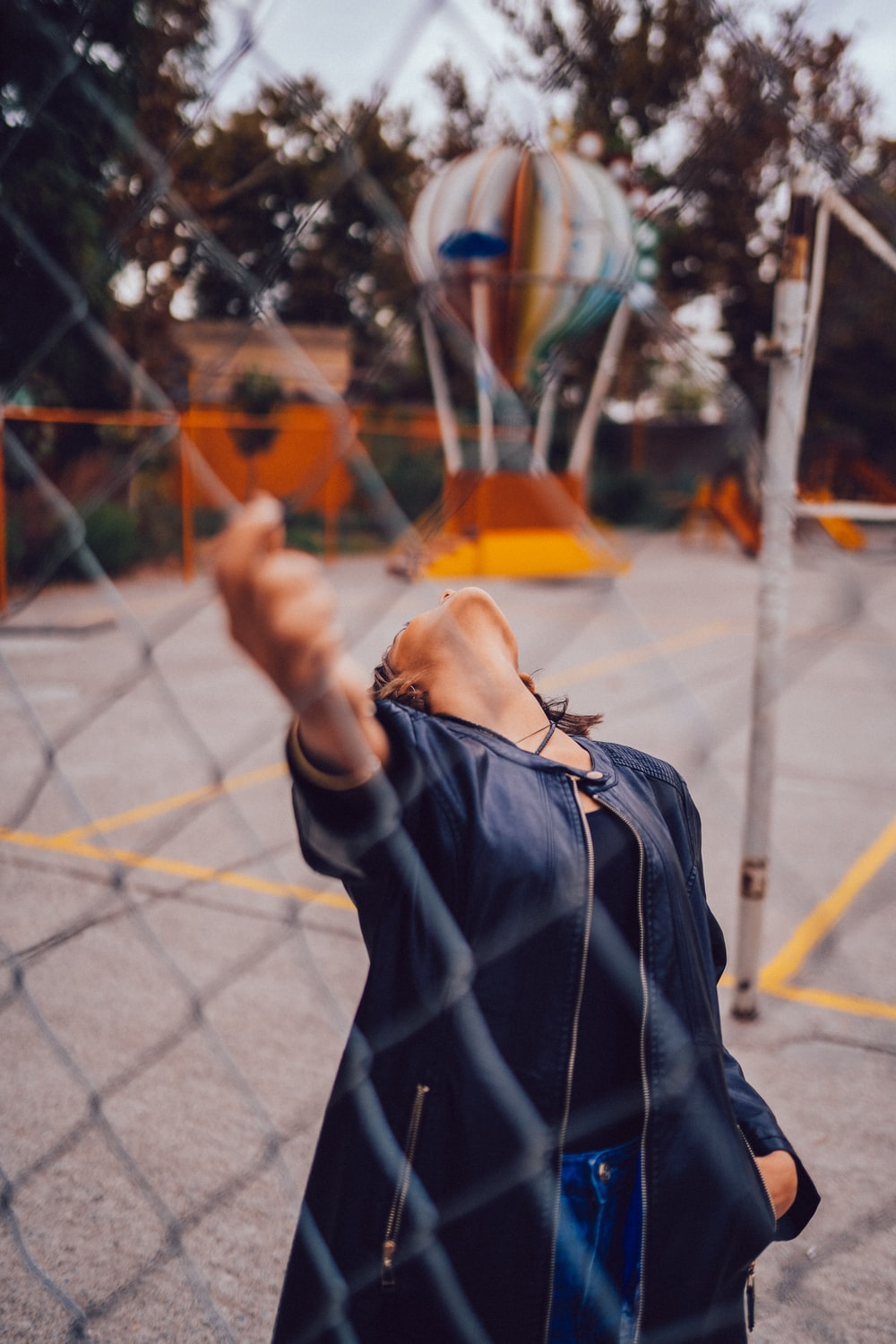 woman holding chainlink fence