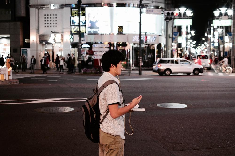 man standing near road wearing earphones