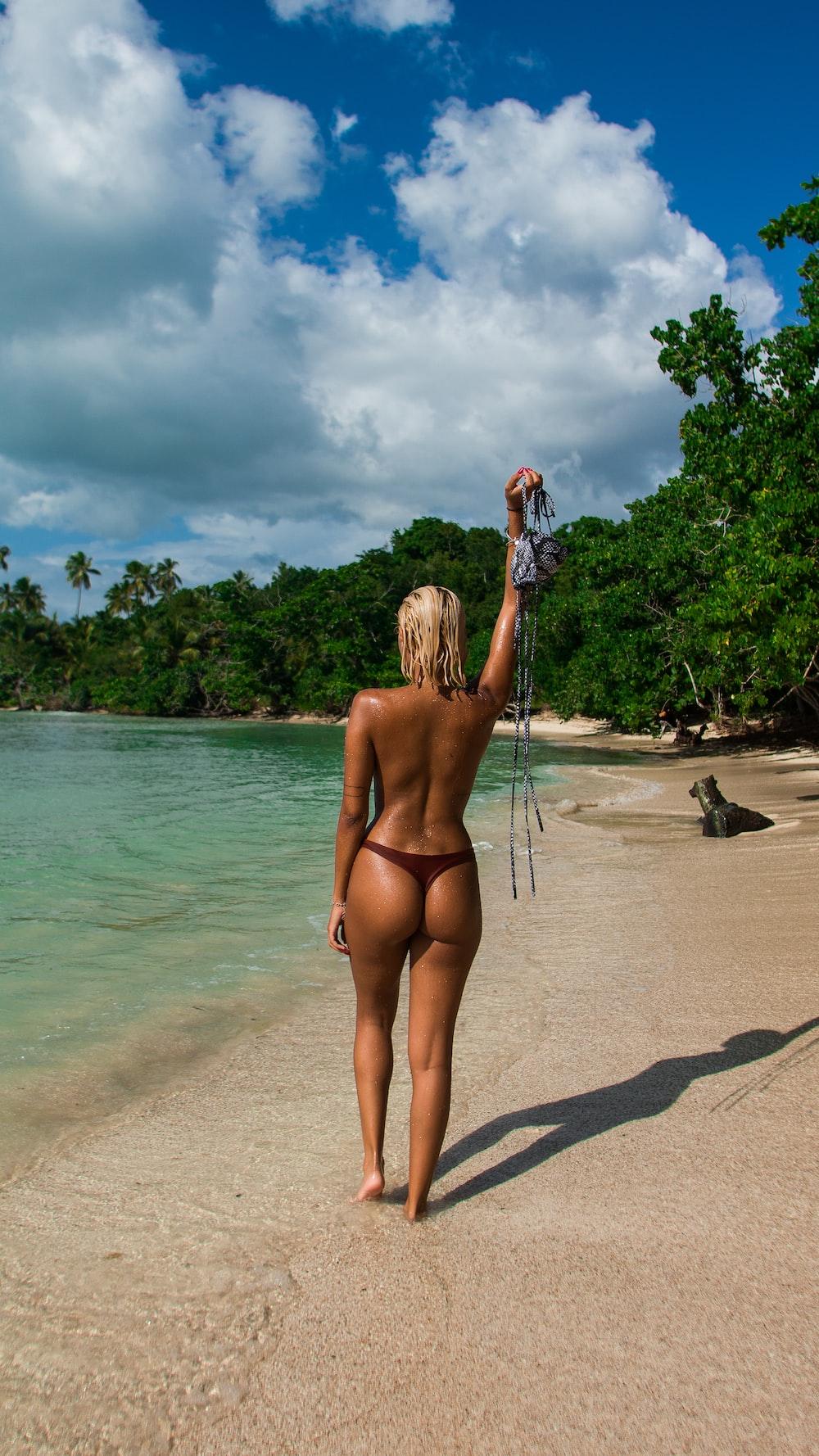woman standing on shoreline raising her bikini top