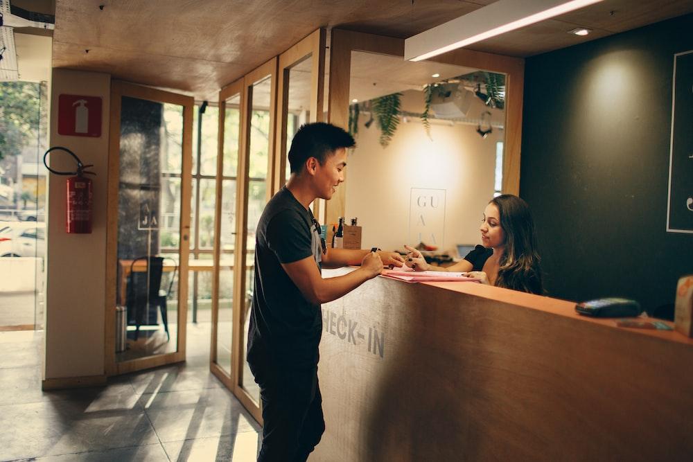 man in black shirt standing beside counter