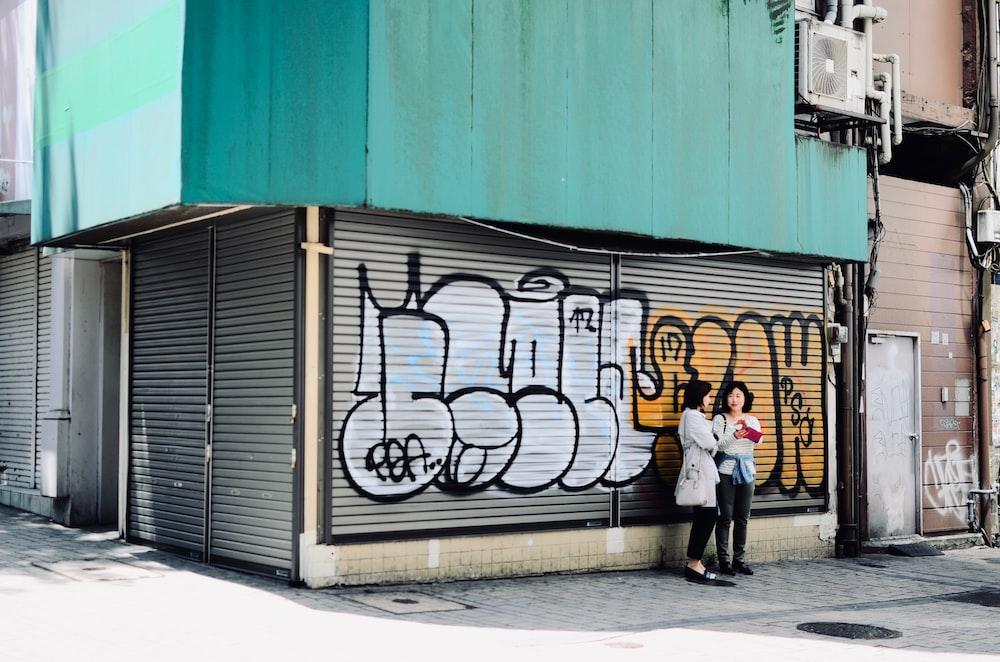 two woman standing near graffiti
