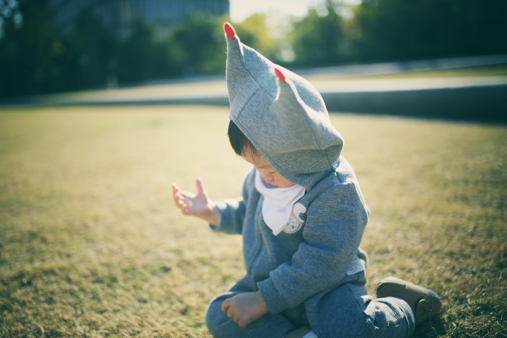 toddler sitting on field