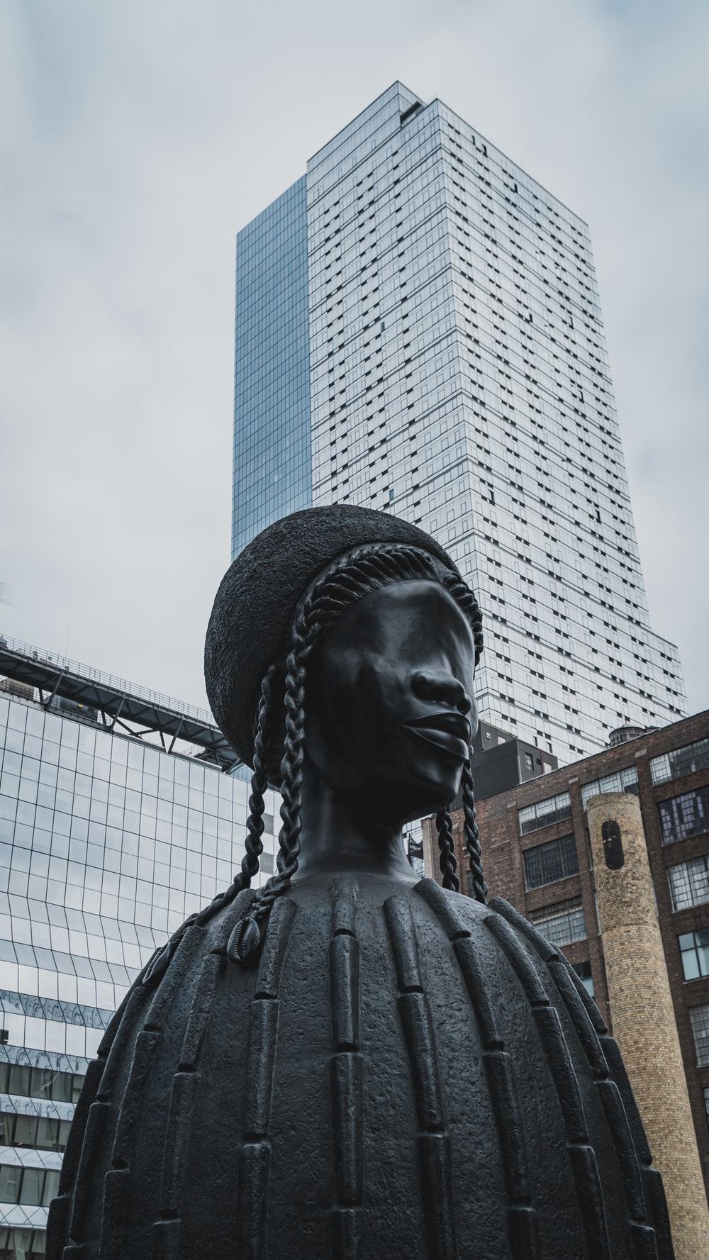 low-angle photography of statue and buildings