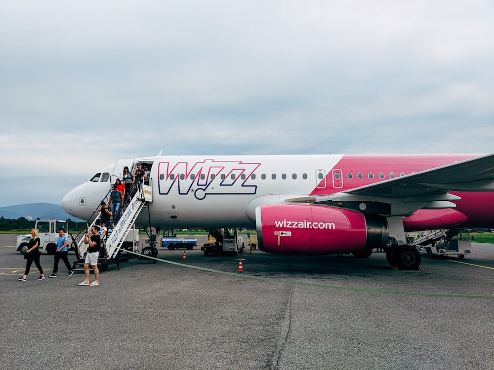 white and pink Wizz Air airliner disembarking passengers