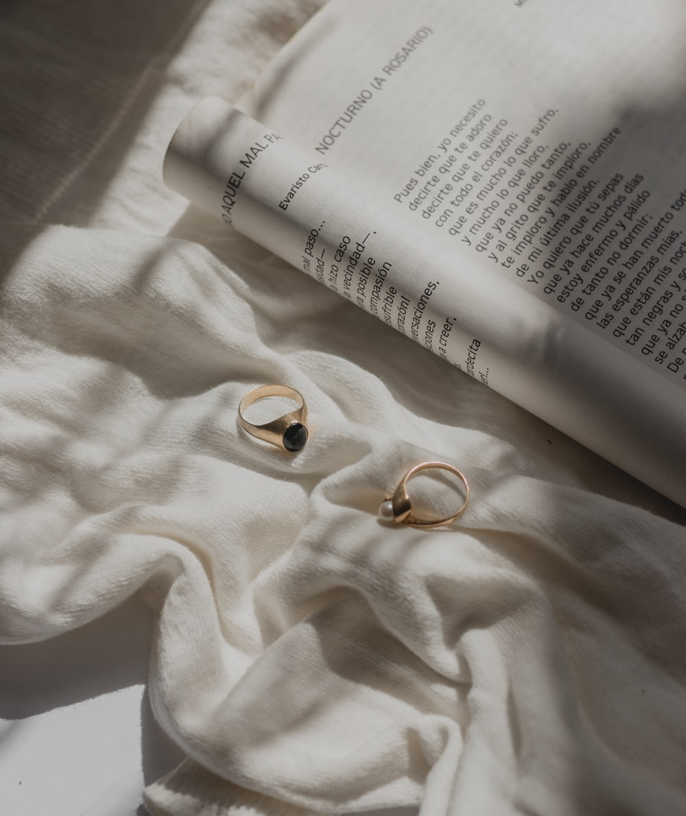 gold-colored rings near open book