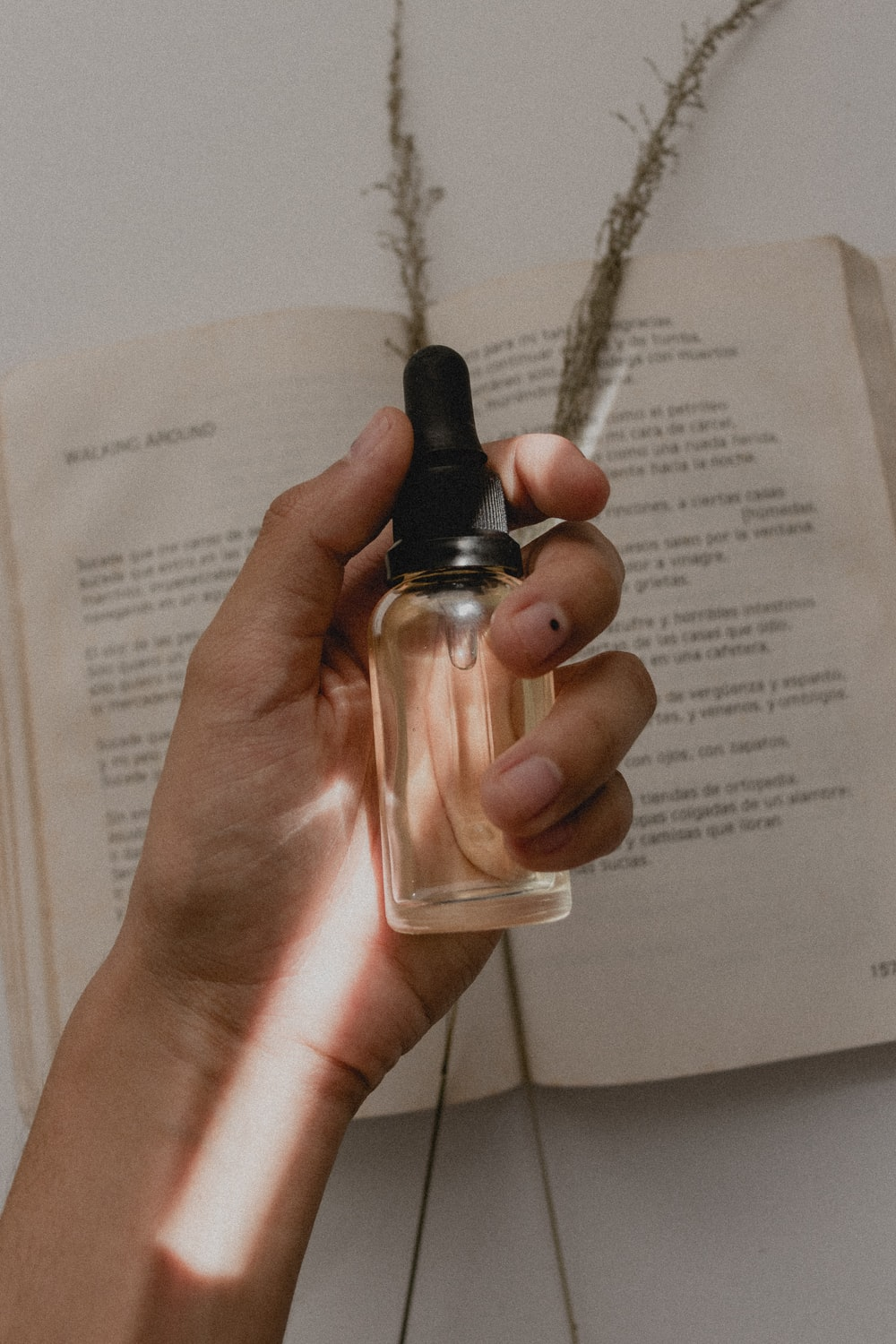 person holding small clear drop bottle