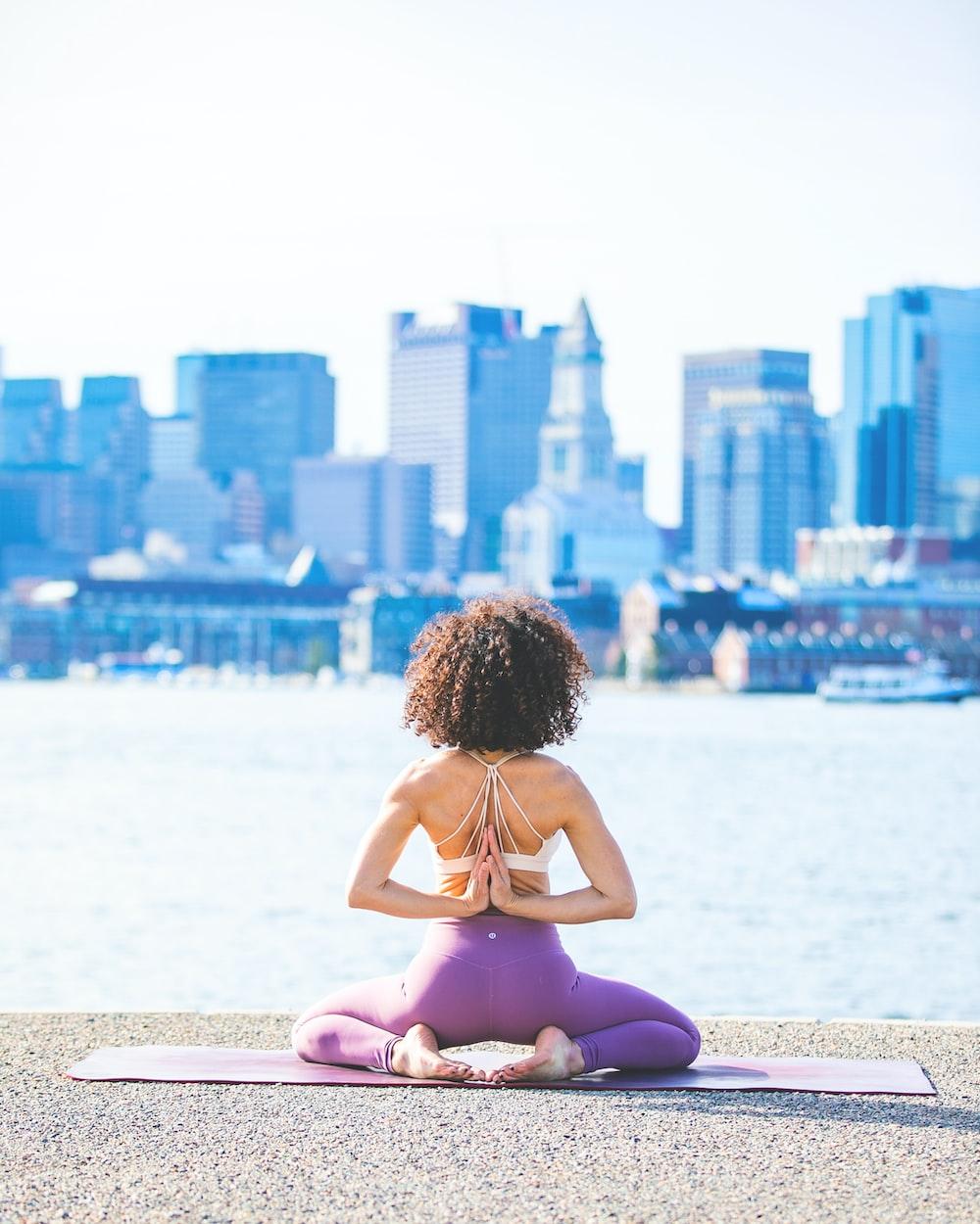 woman doing yoga facing calm body of water