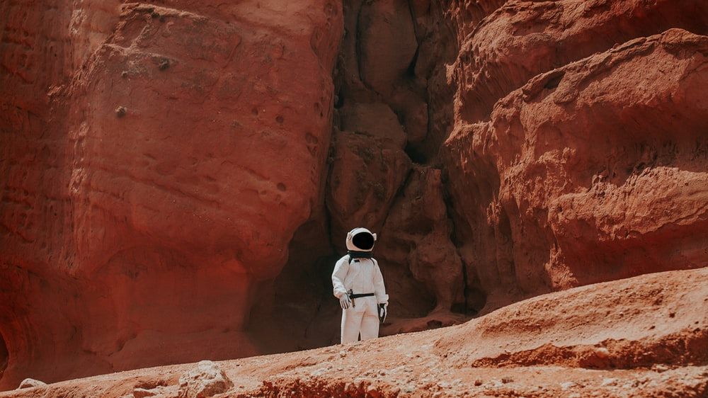 photography of astronaut standing beside rock formation during daytime