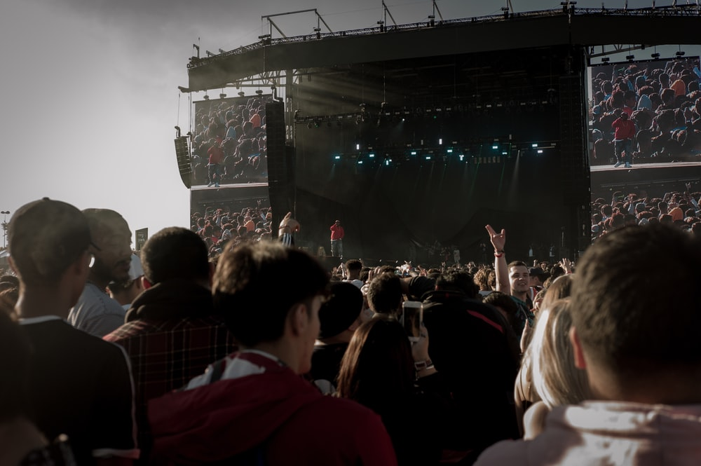 crowd in front of black stage during daytime