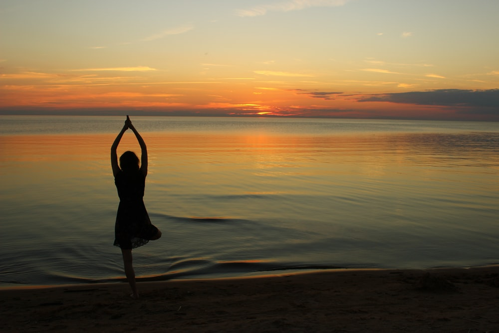woman doing yoga near calm body of water during golden hour