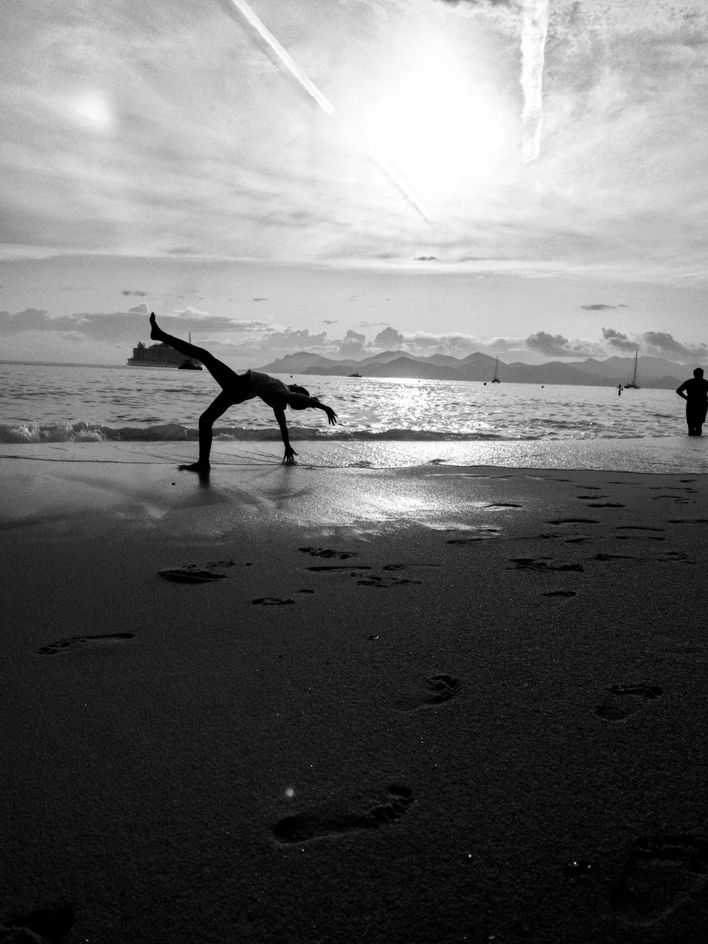 grayscale photography of person bending on shore during daytime