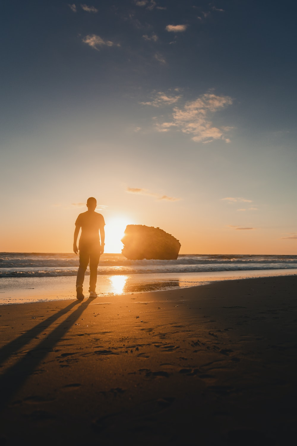 person standing at the beach during golden hour