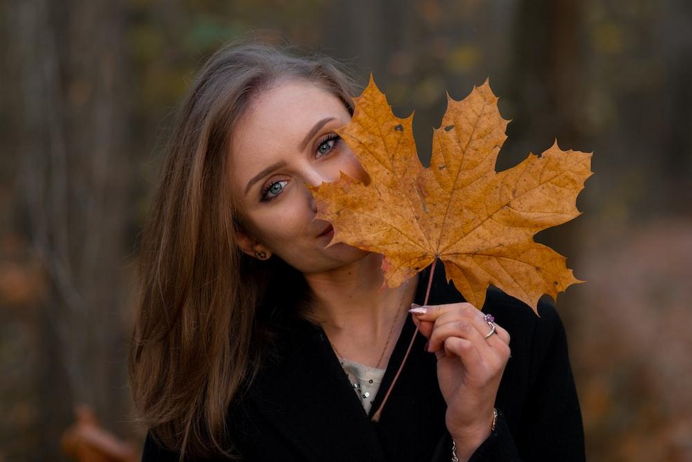 woman holding fallen brown leaf