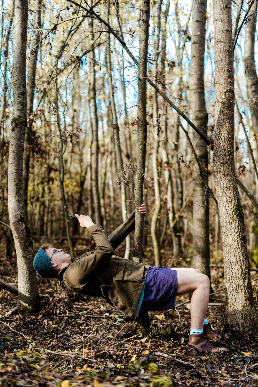 man holding onto tree while lying down