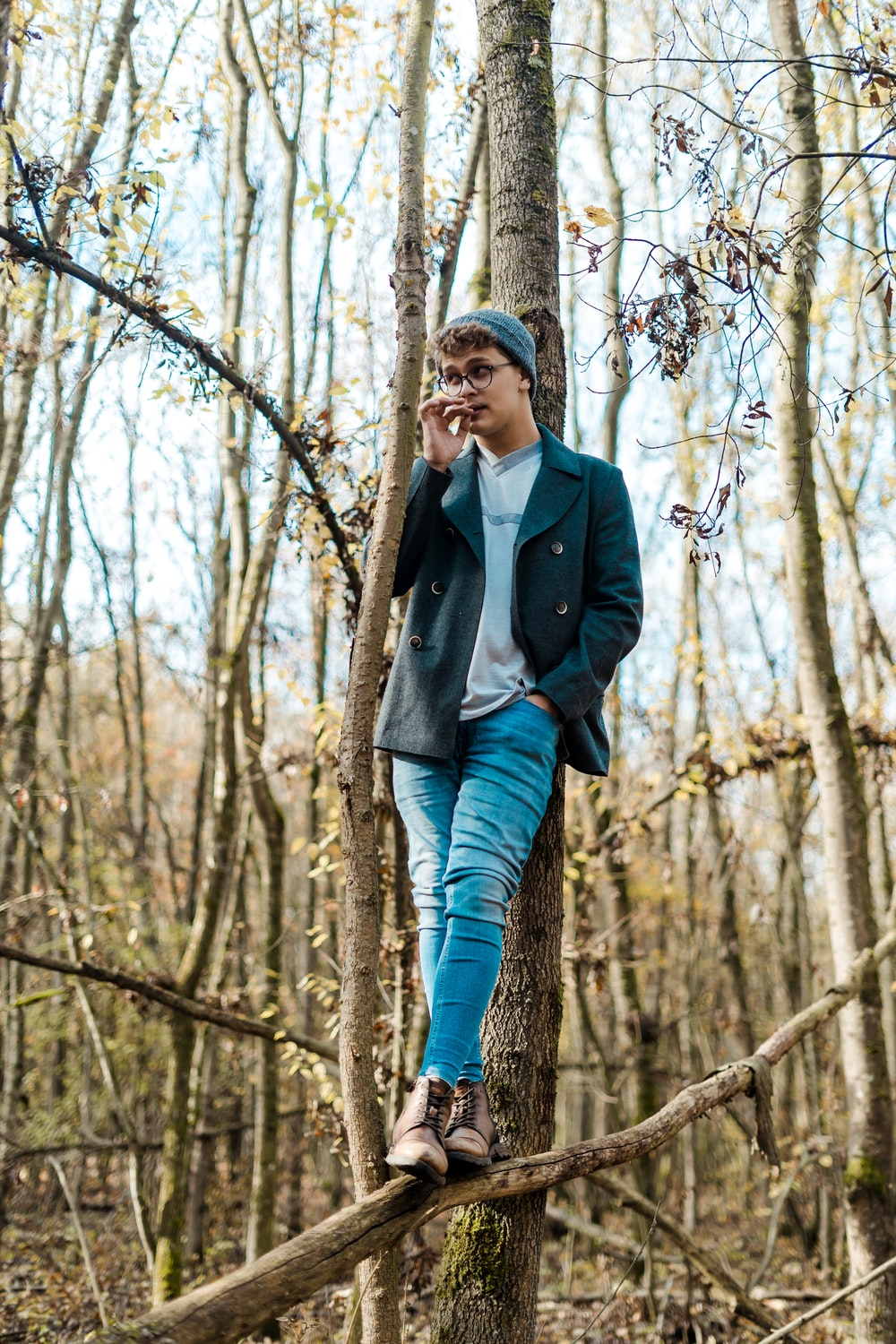 woman in black coat and blue jeans standing on wood log beside tree