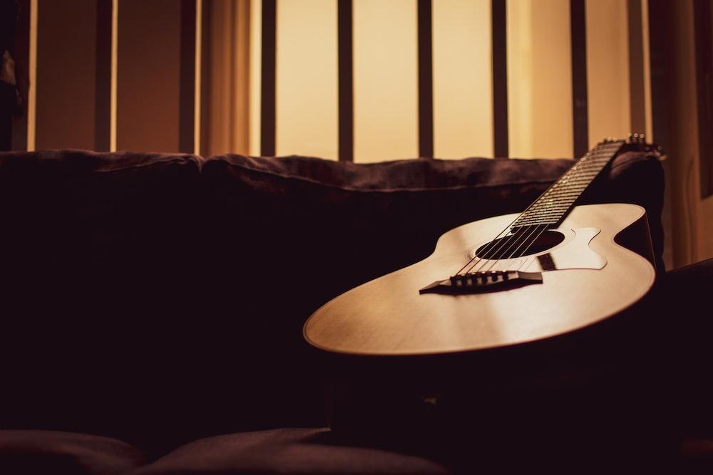 acoustic guitar on sofa