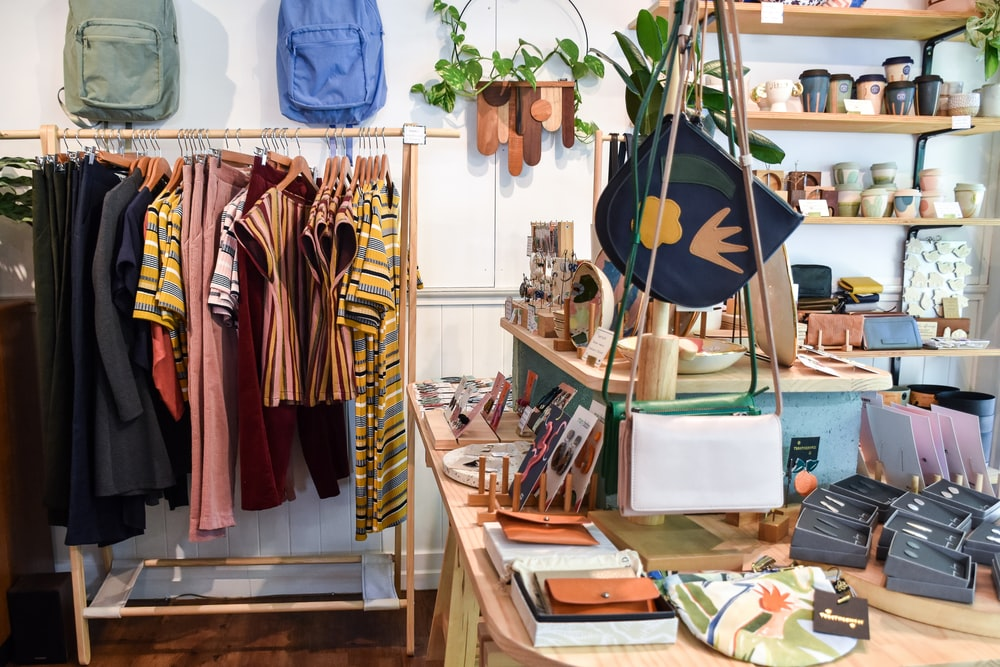 assorted-colored clothes on rack near brown wooden table