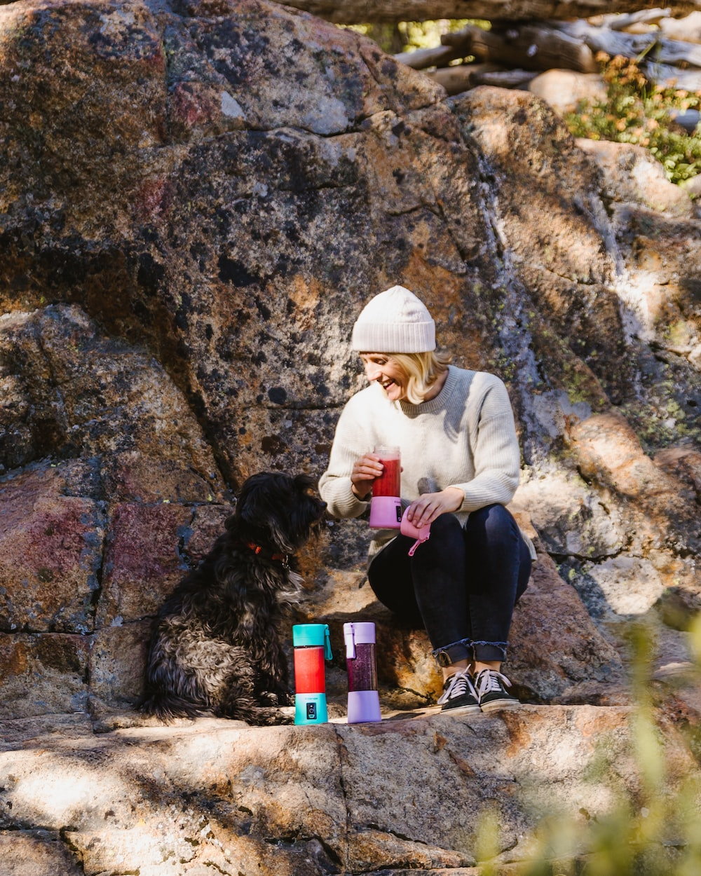 sitting woman on rock by dog during daytime