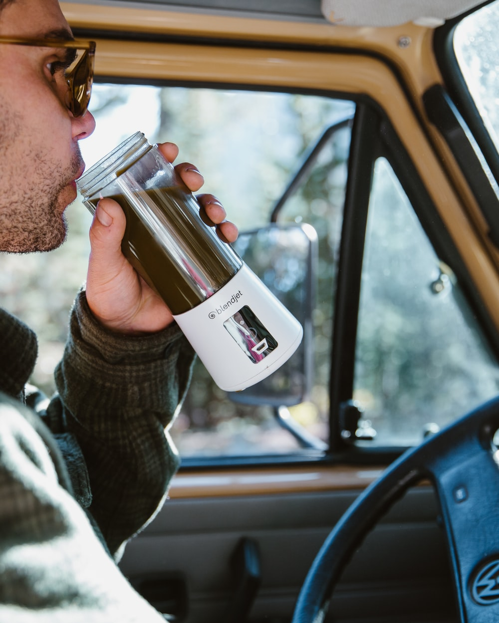 man drinking on single-serve blender while sitting inside vehicle