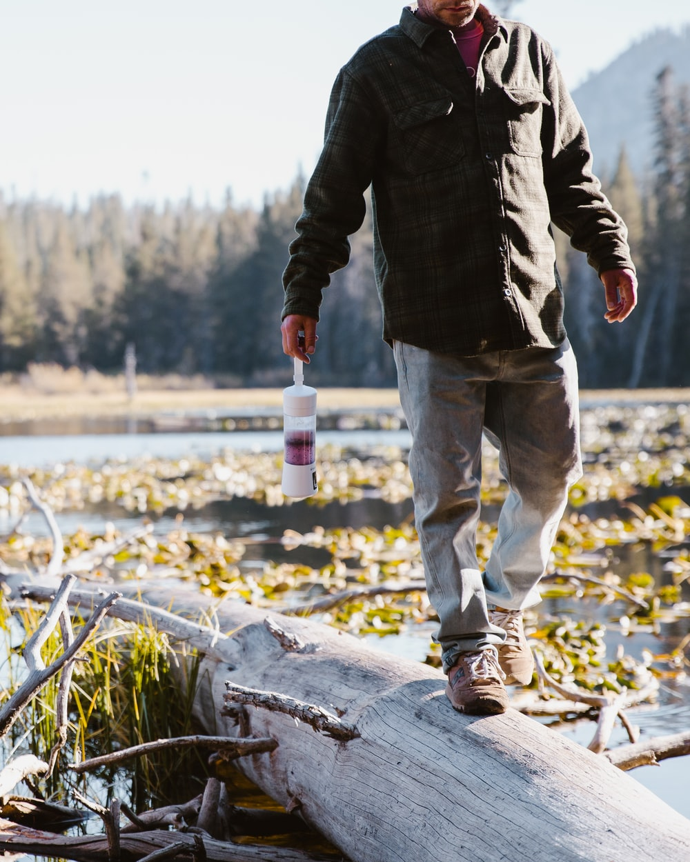 man in black jacket and gray jeans holding white bottle while crossing wood log