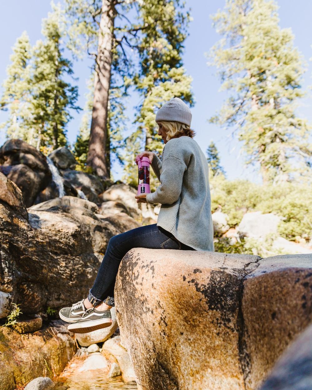 woman sitting on rock while holding blender tumbler