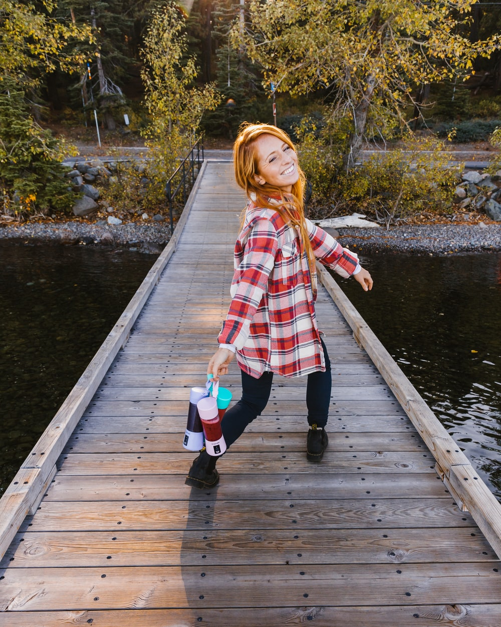 smiling woman wearing plaid shirt walking on bridge