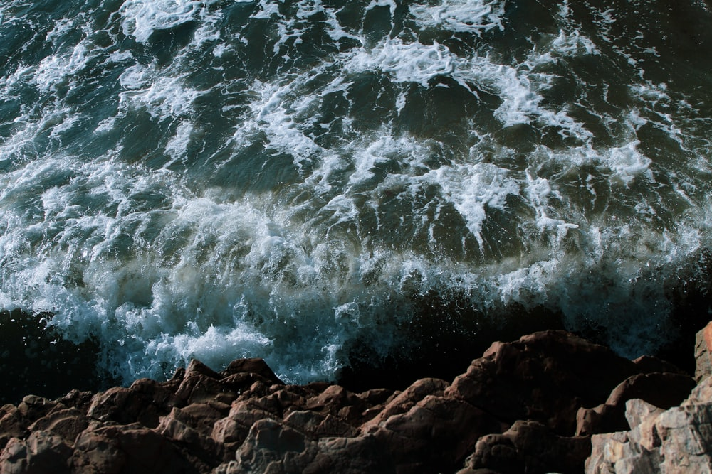 aerial photography of cliff and body of water