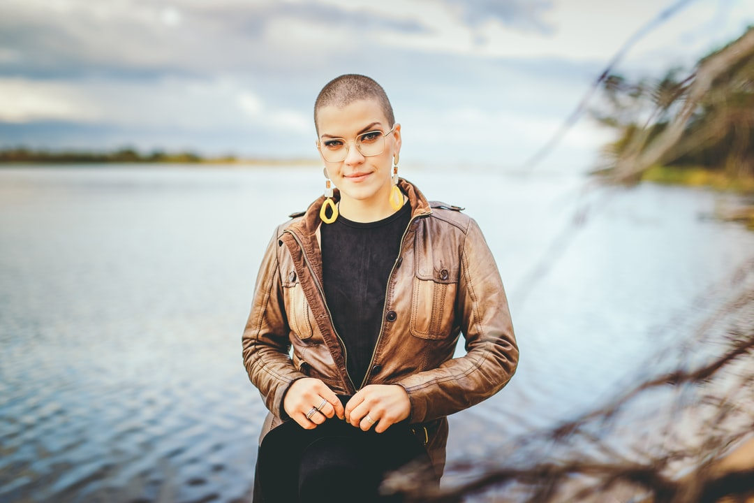 Stylish and beautiful girl with short hair and glasses looking stunning near the river Gauja in outdoor photoshoot.