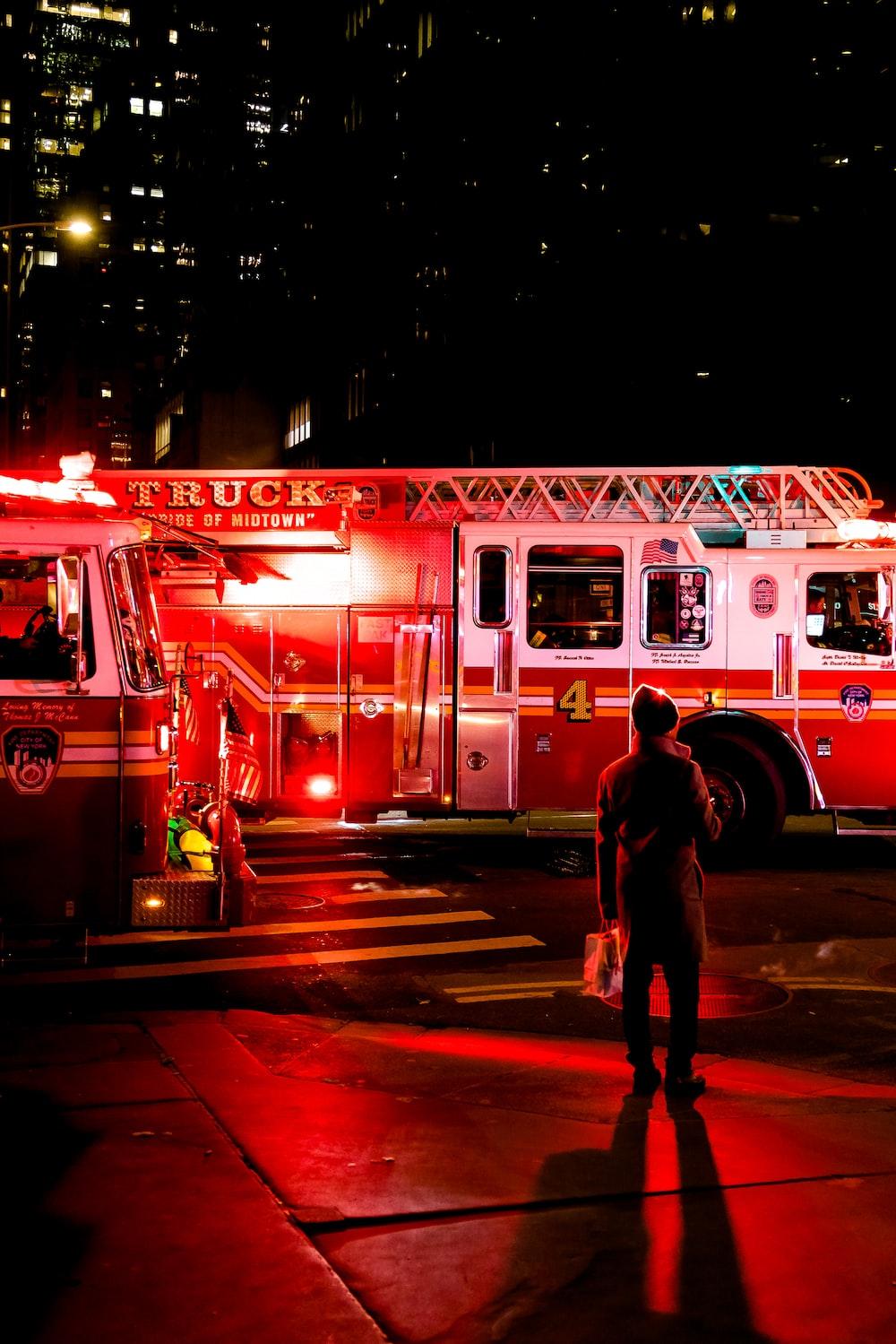 person standing near lighted firetruck