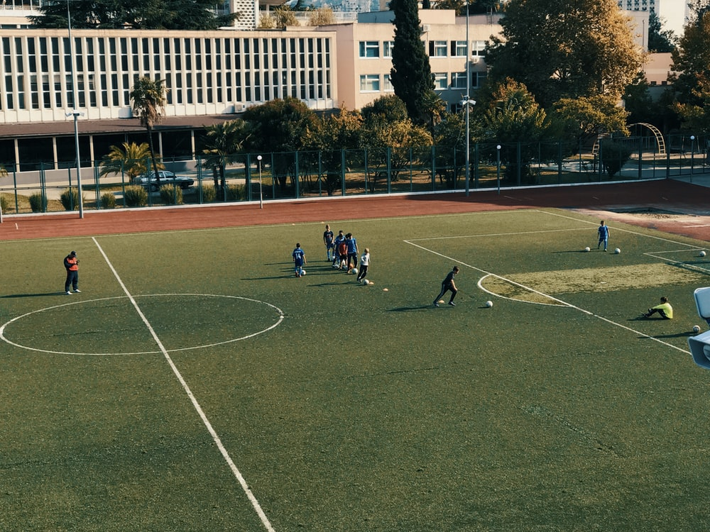 people playing soccer on open field