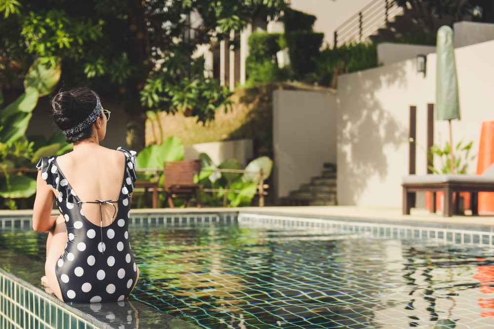 woman sitting beside pool near house during daytime