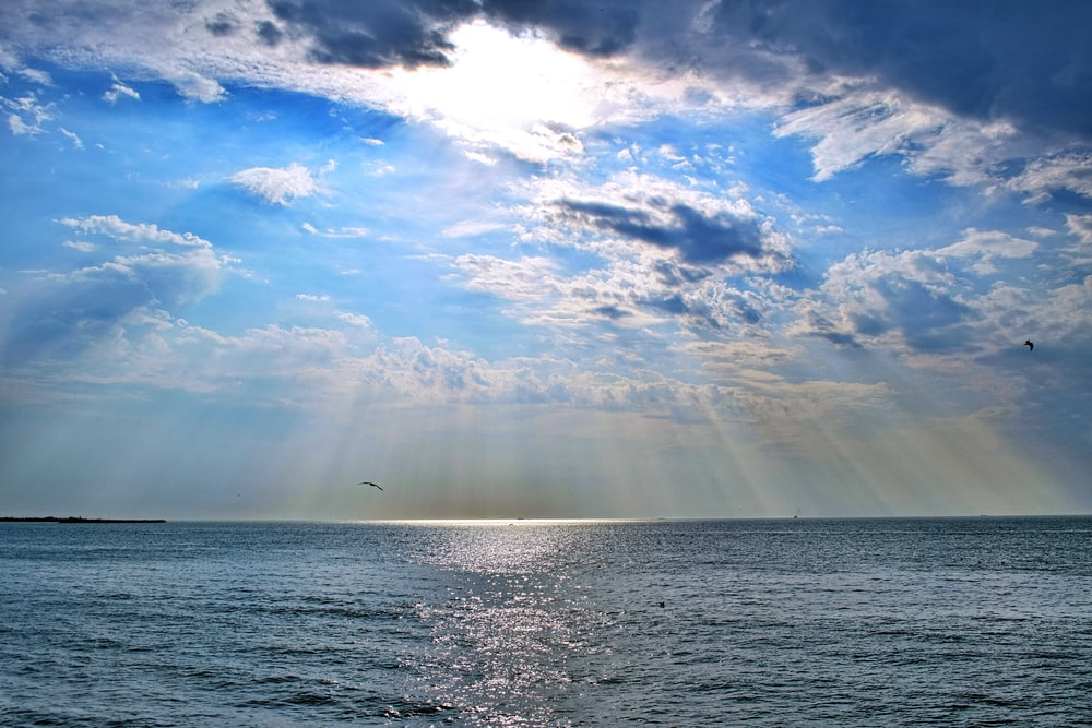 view photography of ocean under cloudy sky