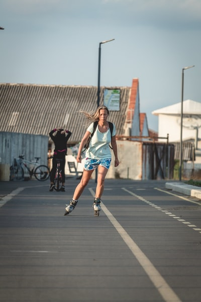 woman riding roller blades on road during daytime