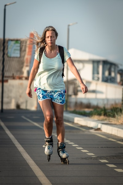 woman in roller blades on road during daytime