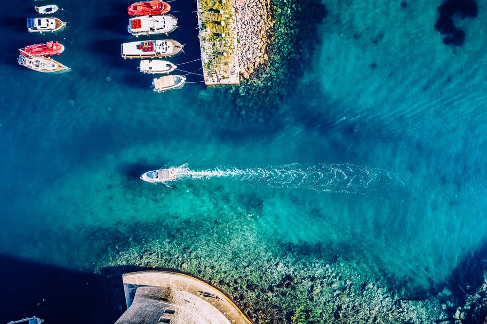aerial photography of assorted-colored boats and yachts on blue body of water during daytime