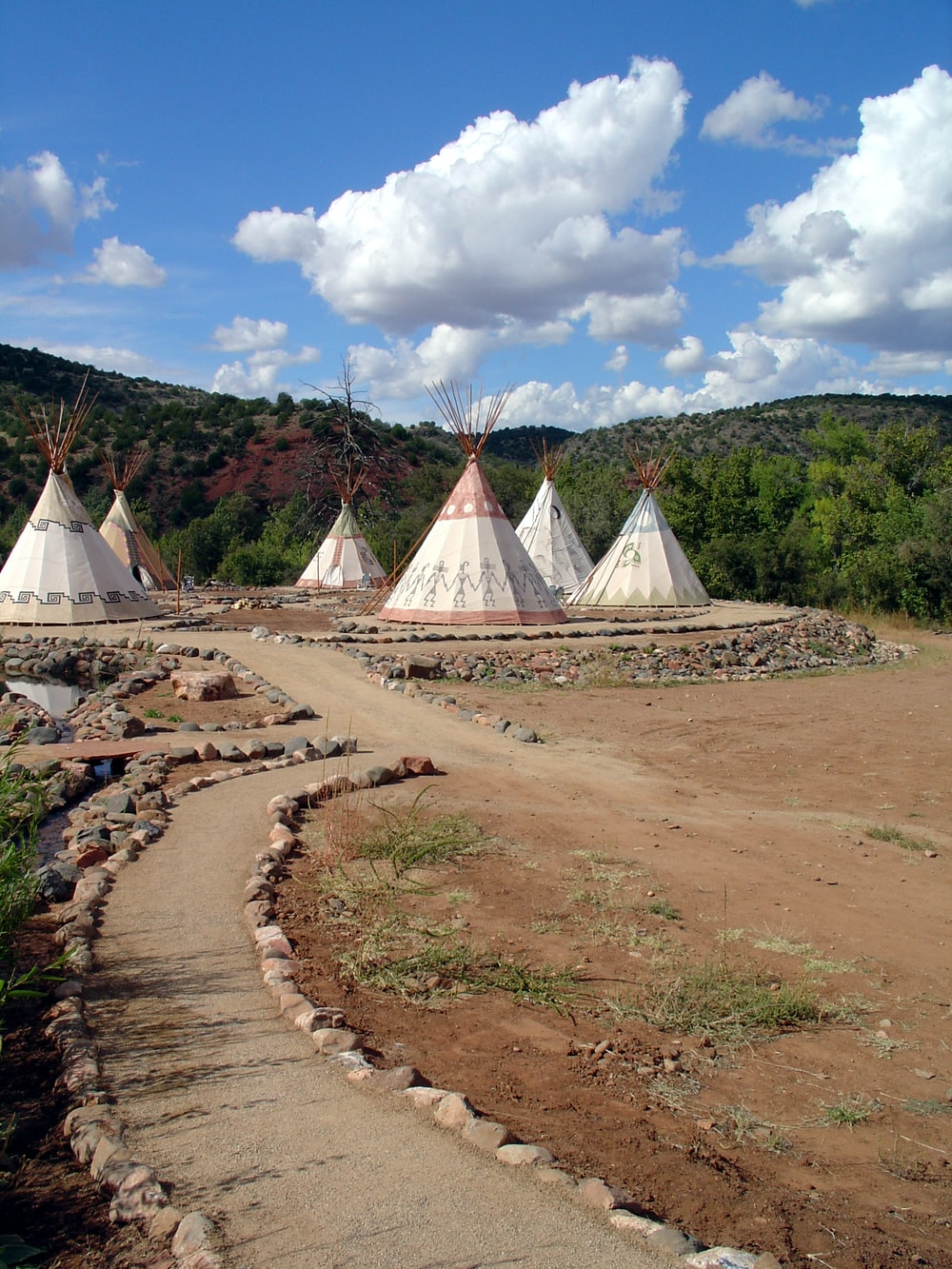 six white teepee tents on ground