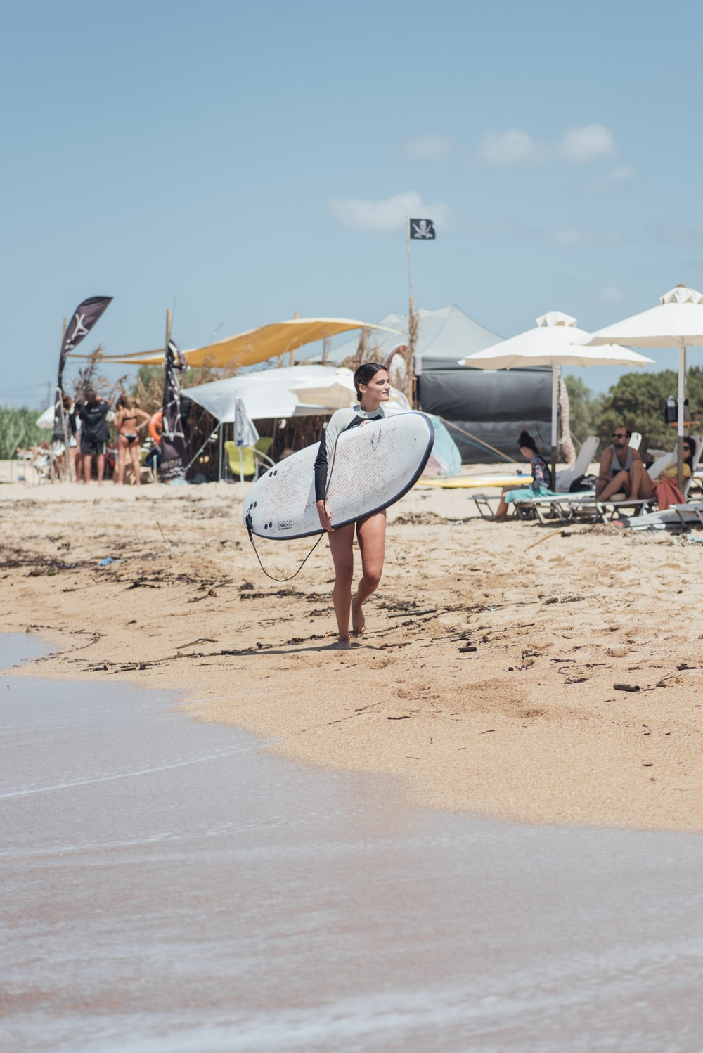 woman holding white surfboard during daytime