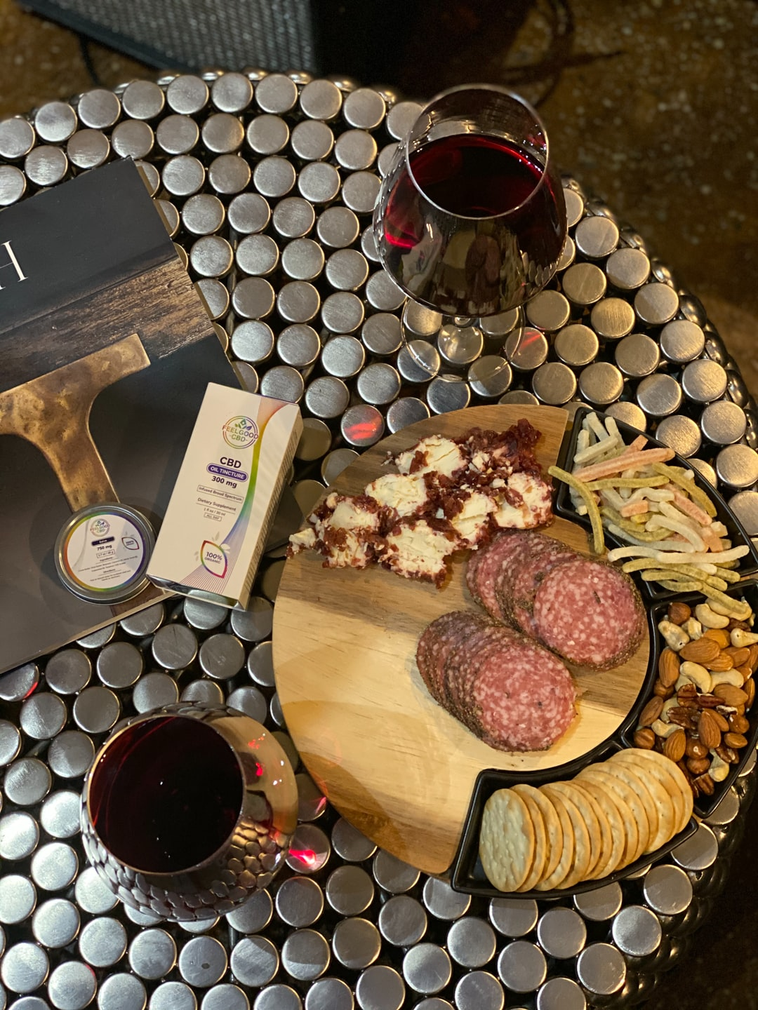 Coffee Table with wine, CBD oil, and a plate of assorted meats, cheeses, crackers, and nuts.