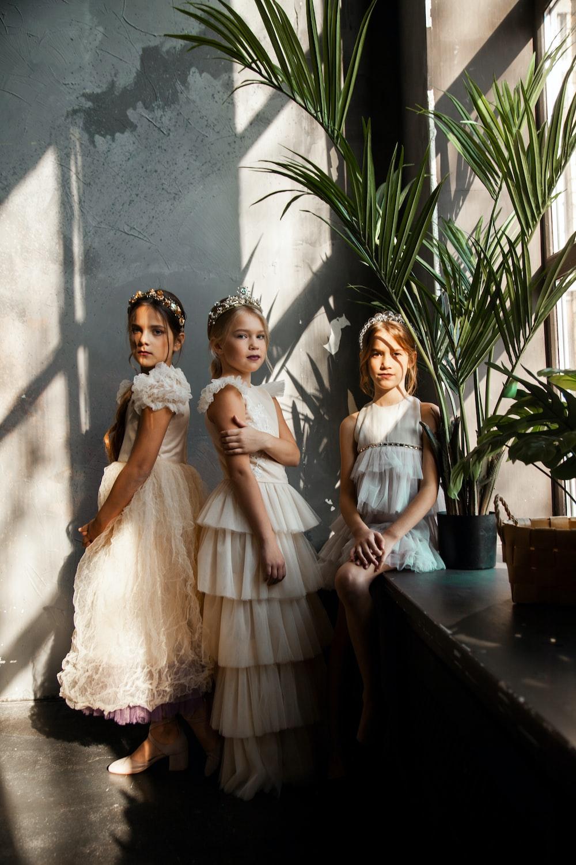 three girls wearing white sleeveless dresses standing beside window