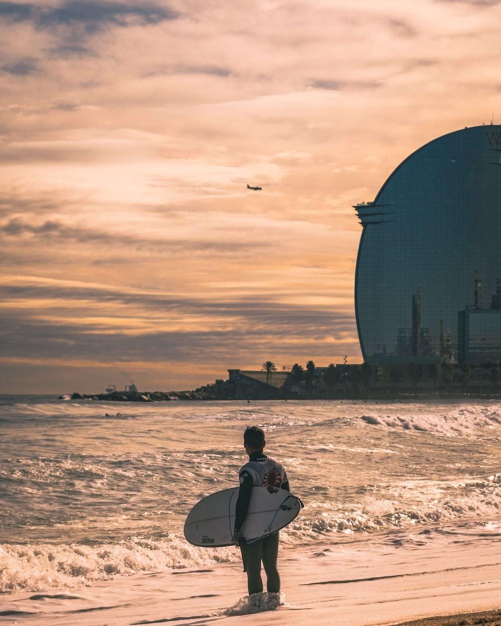 man standing on the seashore holding surfboard