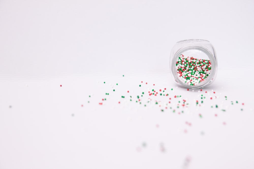 multicolored sprinkles pouring from clear jar