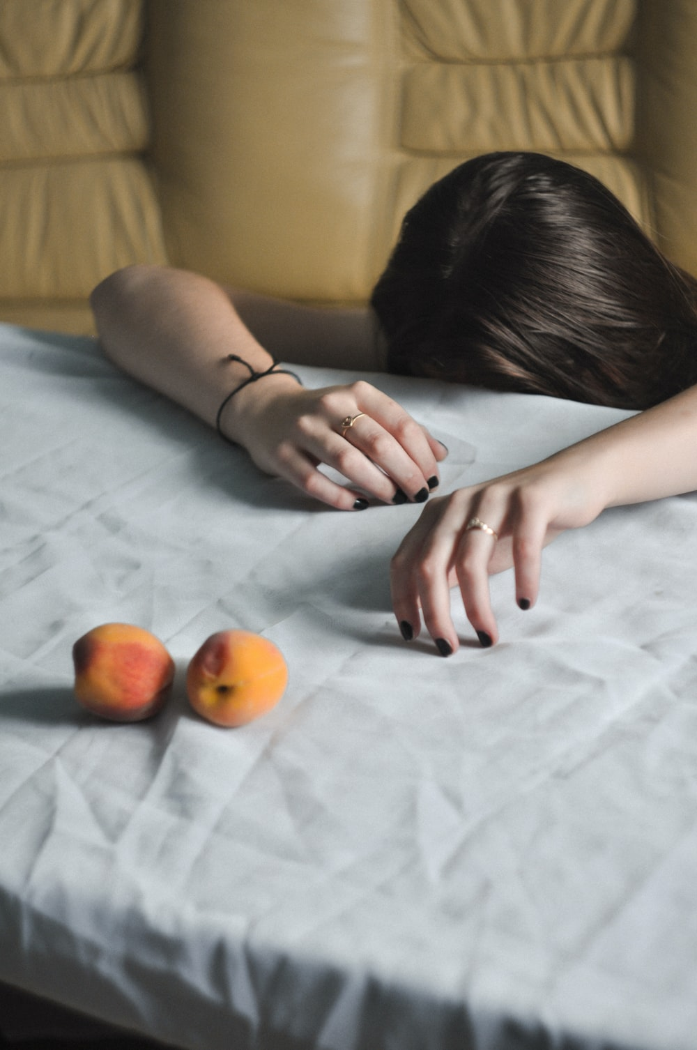 woman leaning on white textile near fruits