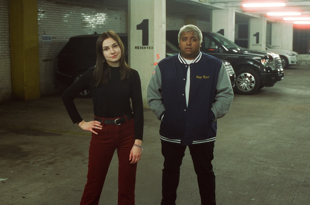 woman and man standing near parked cars at the indoor parking lot