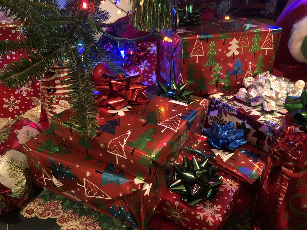 assorted-colored gift boxes near Christmas tree