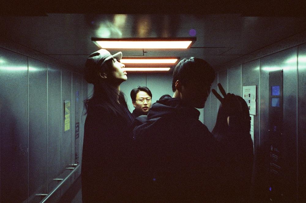 people standing inside gray elevator