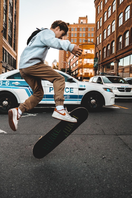 man in gray sweater doing skateboard trick