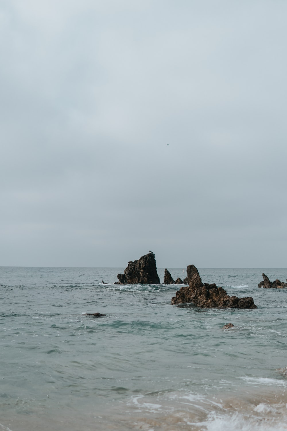 brown rock formations on blue sea during daytime