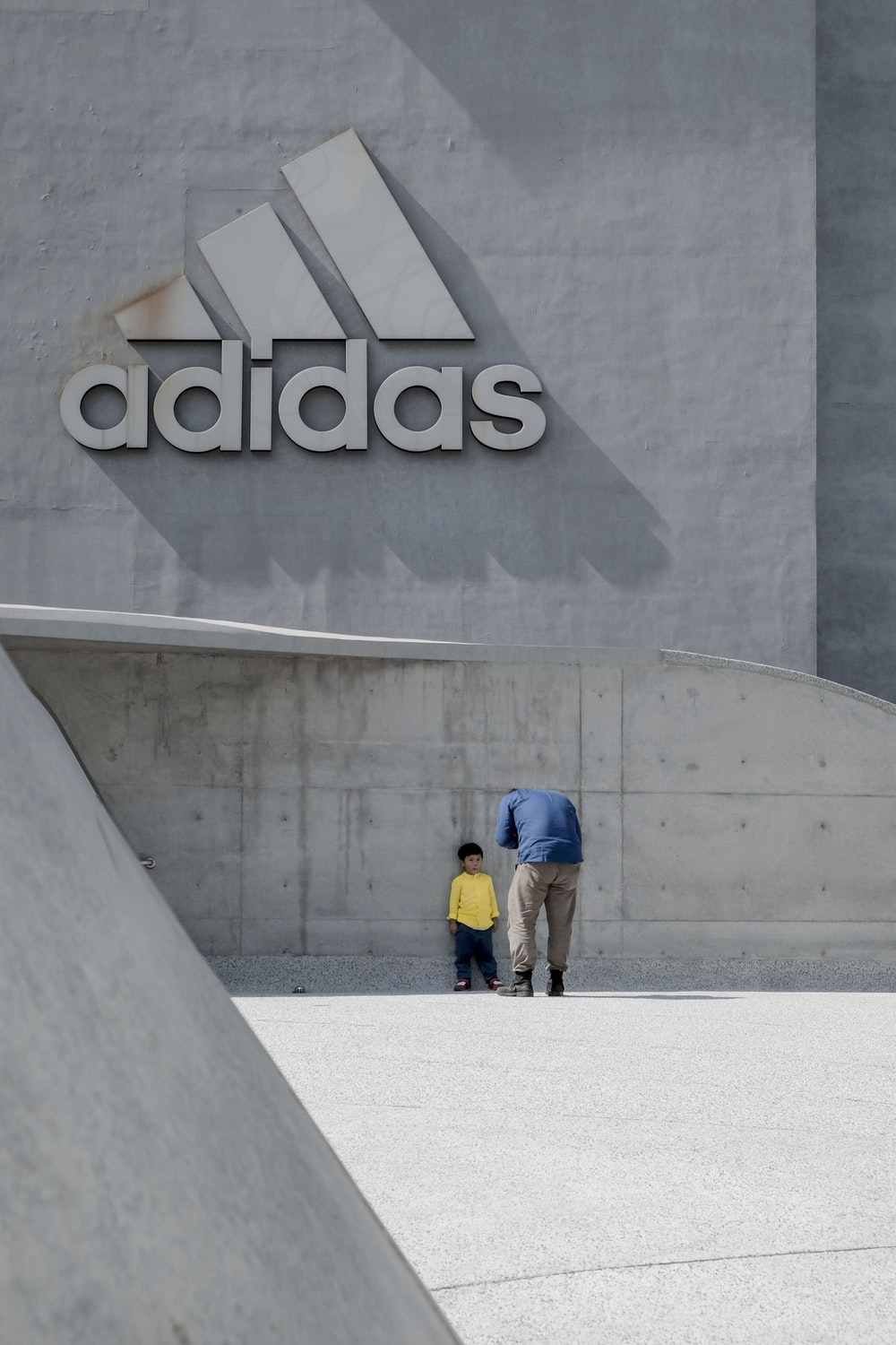 man standing in front of boy leaning on adidas building wall