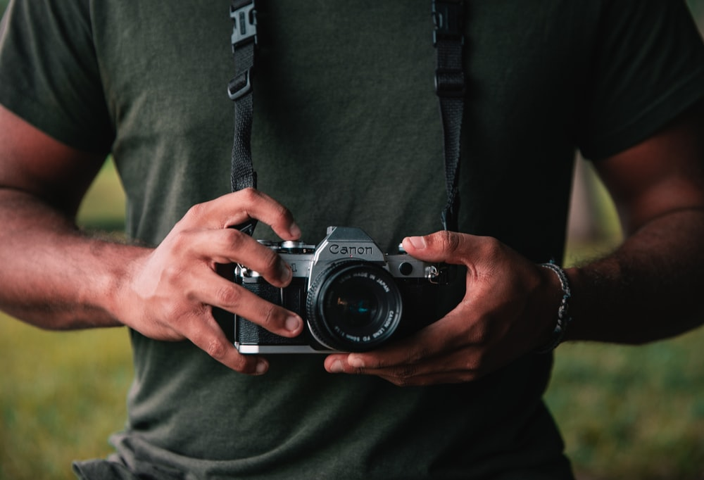 shallow focus photo of person holding black Canon SLR camera